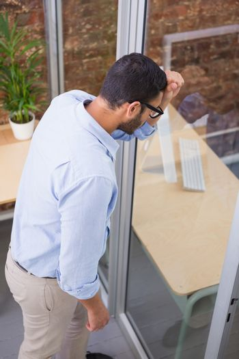 Thoughtful businessman standing against glass wall at office