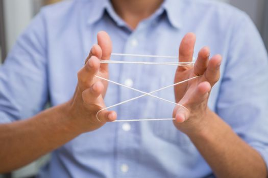 Close up mid section of man holding tangled string