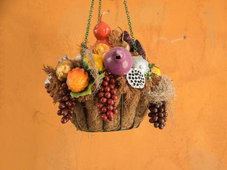 closed up the basket of artificial fruits is hanging on the wall