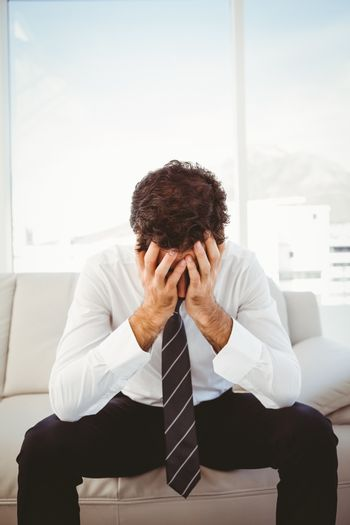Frustrated businessman with head in hands