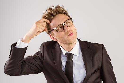 Young geeky businessman scratching his head