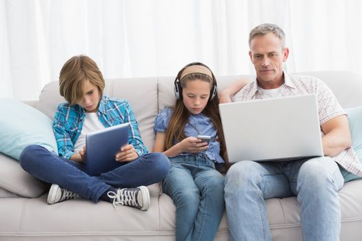 Family focus on wireless technology at home in the living room