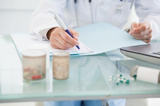 Doctor filling out prescriptions
