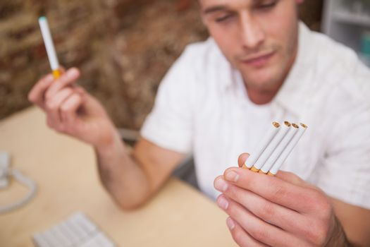 Man deciding between electronic or normal cigarettes
