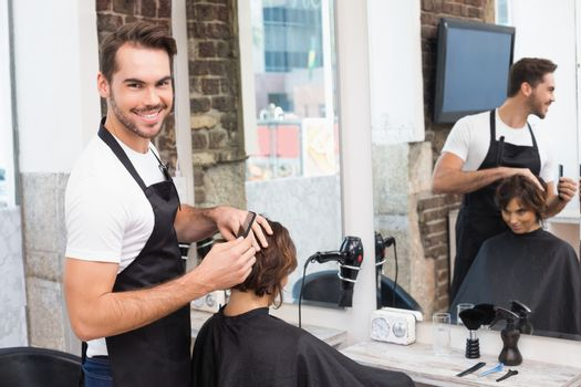 Handsome hair stylist with client