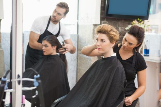 Hairdresser smiling and styling customers hair