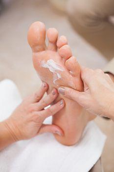 Pedicurist rubbing massage cream