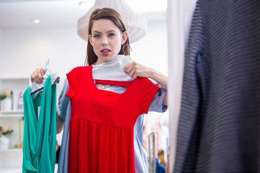 Woman deciding between two dresses