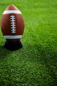 American football standing on holder