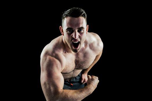 Handsome bodybuilder flexing and shouting