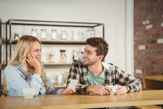 Smiling hipsters sitting and talking at coffee shop