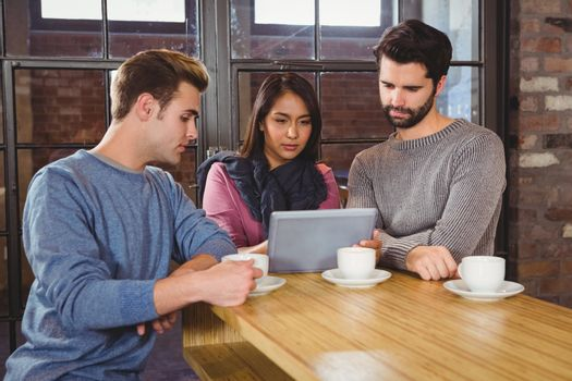 Group of friends enjoying a coffee with a tablet