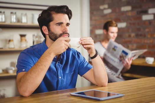 Young man having cup of coffee using tablet