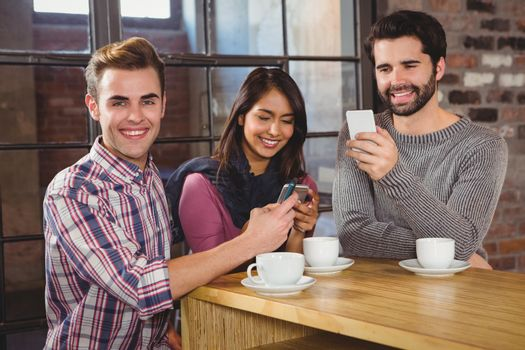 Group of friends looking at their smartphone