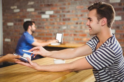 Paying for a croissant and a coffee with his smartphone