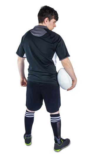 Back turned rugby player holding a ball