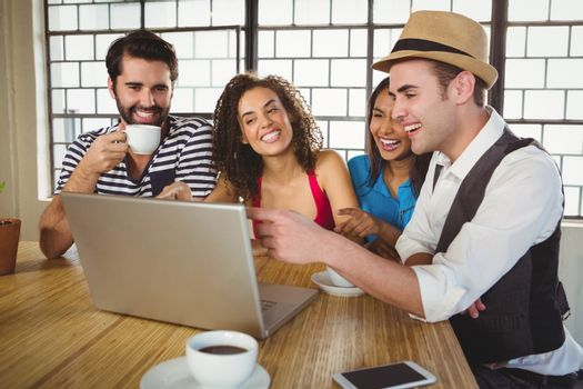Smiling friends looking at laptop and having coffee