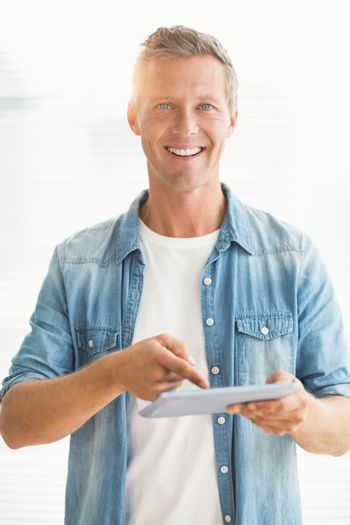 Smiling businessman scrolling on a tablet