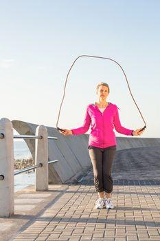 Sporty woman skipping at promenade