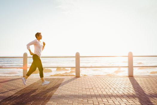 Sporty woman jogging at promenade