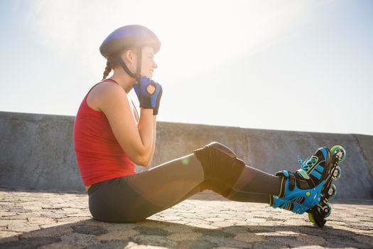 Sporty blonde skater sitting on ground and fastening helmet