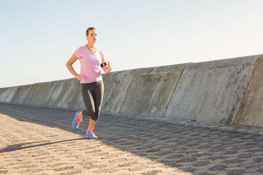 Sporty blonde jogging at promenade