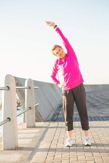 Smiling sporty woman stretching at promenade