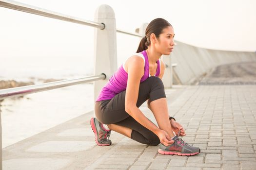Fit woman tying shoelace at promenade