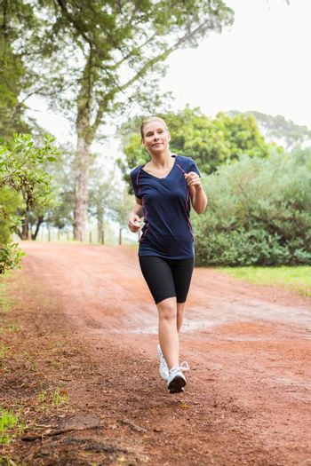 Athletic woman running on a footpath