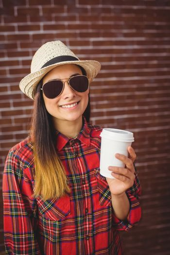 Beautiful hipster with disposable coffee