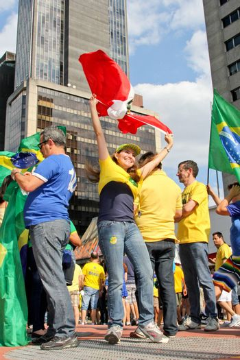 SAO PAULO, BRAZIL August 16 2015: An unidentified group of people with flags and yellow and green clothes in the protest against federal government corruption in Sao Paulo Brazil.