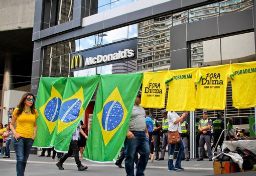 SAO PAULO, BRAZIL August 16, 2015: An unidentified woman walks in front of a flag vendor in the protest against federal government corruption in Sao Paulo Brazil. Protesters call for the impeachment of President Dilma Rousseff.