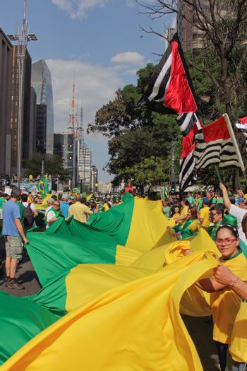 SAO PAULO, BRAZIL August 16, 2015: An unidentified group of people hold a big flag in the protest against federal government corruption in Sao Paulo Brazil. Protesters call for the impeachment of President Dilma Rousseff.