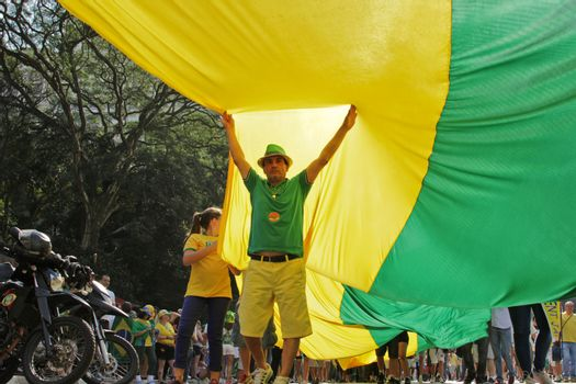 SAO PAULO, BRAZIL August 16 2015: An unidentified man below of a big flag in the protest against federal government corruption in Sao Paulo Brazil. Protesters call for the impeachment of President Dilma Rousseff.