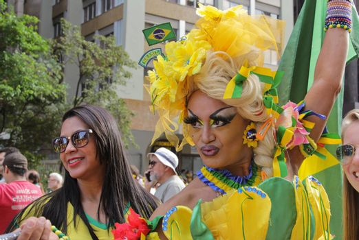 SAO PAULO, BRAZIL August 16, 2015: A drag queen called Charlene Blue with yellow and green costume poses for pictures and selfies in the protest against federal government corruption in Sao Paulo Brazil.