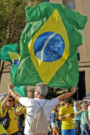 SAO PAULO, BRAZIL August 16, 2015: An unidentified man with a flag in the protest against federal government corruption in Sao Paulo Brazil.