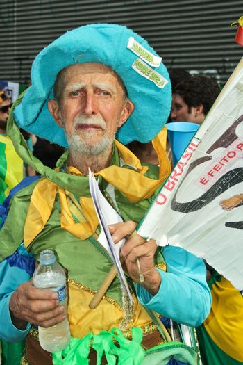 SAO PAULO, BRAZIL August 16, 2015: An unidentified man with yellow green and blue costume in the protest against federal government corruption in Sao Paulo Brazil. Protesters call for the impeachment of President Dilma Rousseff.