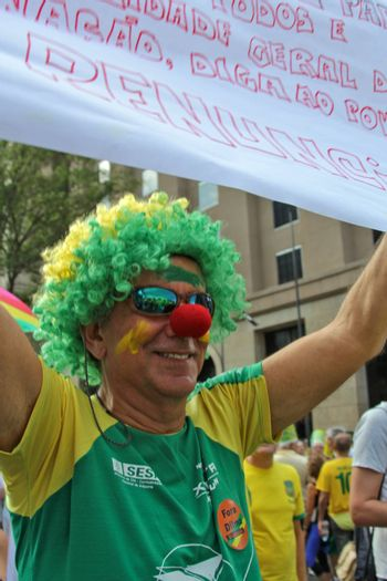 SAO PAULO, BRAZIL August 16, 2015: An unidentified man with yellow and green clown costume in the protest against federal government corruption in Sao Paulo Brazil. Protesters call for the impeachment of President Dilma Rousseff.
