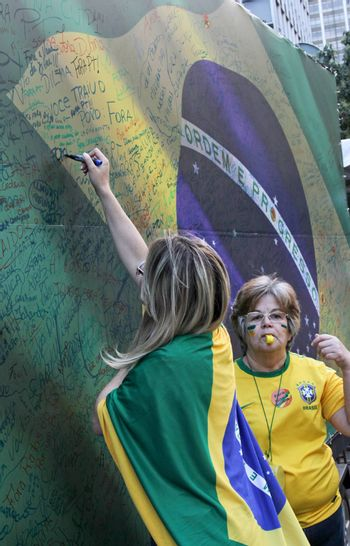 SAO PAULO, BRAZIL August 16, 2015: Two unidentified women  signing a large brazilian flag in the protest against federal government corruption in Sao Paulo Brazil.