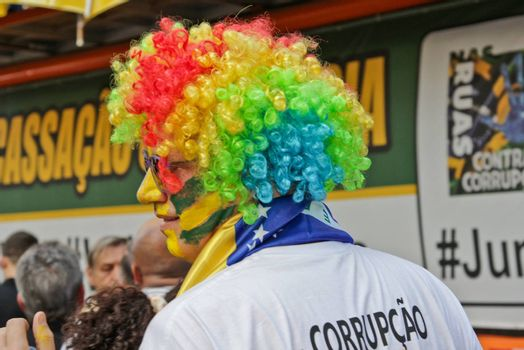 SAO PAULO, BRAZIL August 16, 2015: An unidentified man with yellow and green clown costume in the protest against federal government corruption in Sao Paulo Brazil.