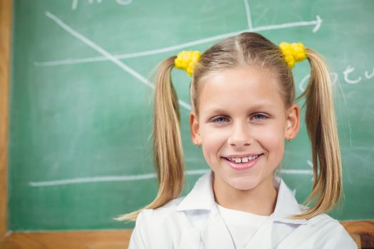 Cute pupil with lab coat in front of chalkboard