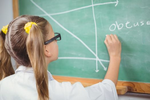 Pupil with lab coat writing on chalkboard in a classroom