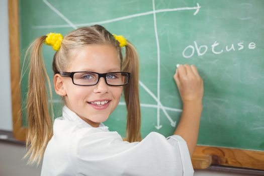 Cute pupil with lab coat writing on chalkboard