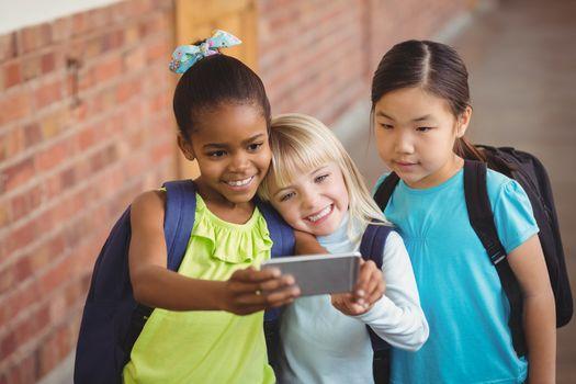 Cute pupils taking selfies at corridor in school
