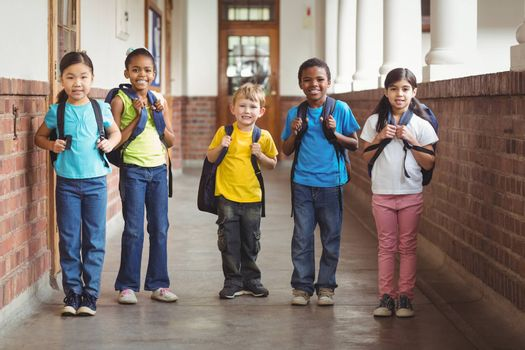 Portrait of cute pupils with schoolbags standing at corridor in school
