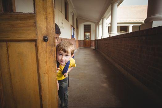Happy pupils peeking at the corridor