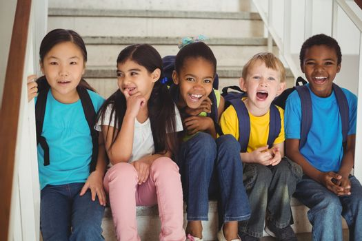 Portrait of happy pupils laughing and sitting on stairs in school