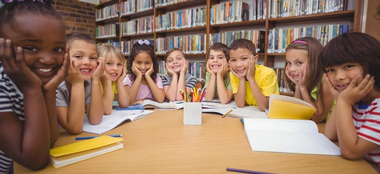 Pupils working together at desk in library at the elementary school