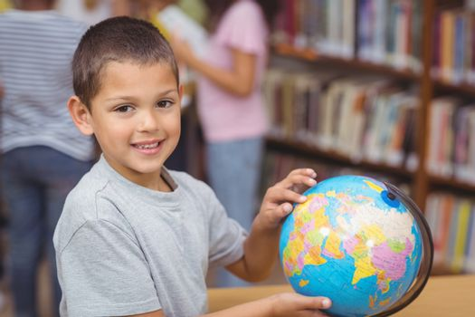 Pupil in library with globe