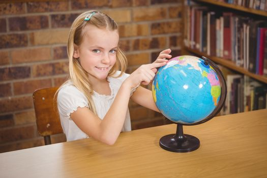 Students pointing to places on a globe